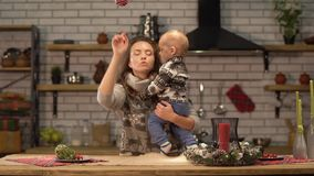 Pretty young woman lifts up the baby in her arms standing in modern kitchen showing to son bright red Christmas tree toy stock footage