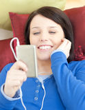 Pretty young woman listening music lying on a sofa Royalty Free Stock Photo