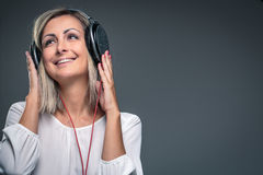 Pretty, young woman listening to her favorite music on hi-fi headphone Stock Image