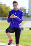 Pretty young woman listening to music after running. Stock Photos