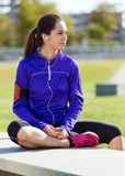 Pretty young woman listening to music after running. Royalty Free Stock Image