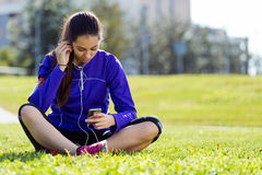 Pretty young woman listening to music after running. Royalty Free Stock Photography