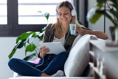 Pretty Young Woman Listening To Music With Her Digital Tablet While Drinking Cup Of Coffee On Sofa At Home Royalty Free Stock Image