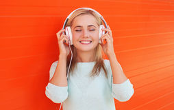 Pretty young woman listens and enjoys the music in headphones Stock Photos