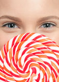 Pretty young woman with lollipop. Isolated Stock Photography