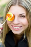 Pretty young woman with lollypop covering her eye Stock Photography