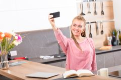 Pretty young woman taking a selfie in the kitchen stock photography