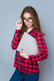 Pretty young woman looking over her glasses Stock Photo