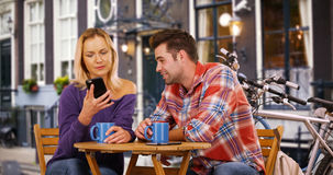 Pretty young woman looking at smartphone while on date with white guy Stock Photography