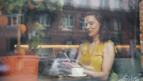 Pretty young woman looking at smartphone screen relaxing in cafe alone. Pretty young woman student is looking at smartphone screen relaxing in cafe alone sitting stock video footage