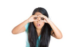Pretty young woman looking for something with wide open eyes and imaginary binocular Stock Photo