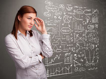 Pretty woman looking at stock market graphs and symbols Stock Photo