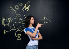 Pretty young woman looking at stock market graphs and symbols Stock Photo