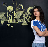 Pretty young woman looking at stock market graphs and symbols Stock Photography