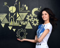 Pretty young woman looking at stock market graphs and symbols Royalty Free Stock Photography