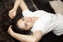 Pretty young Woman lying. Young, beautiful woman, lying on the carpet on the floor, smiling upside-down Stock Photography