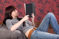 Pretty young woman lying on bean bag reading book Royalty Free Stock Image