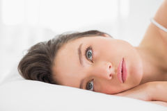 Pretty young woman lying in bed Royalty Free Stock Photos