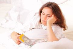 Pretty young woman lying in bed in the morning Royalty Free Stock Photos