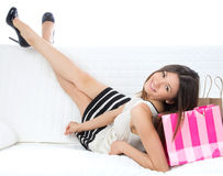 Pretty young woman lying on bed with shopping bags. On a white background Royalty Free Stock Photography
