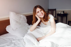 Pretty young woman lying on bed and speaking over cellphone Royalty Free Stock Photography