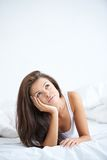 Pretty Young Woman Lying in Bed Thinking stock image