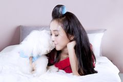 Woman with Maltese puppy on bed. Pretty young woman lying on the bedroom while kissing her Maltese puppy Royalty Free Stock Photography