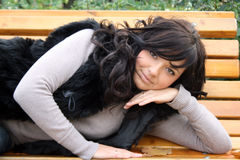 Pretty young woman lying on bench Stock Photo