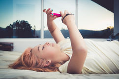 Pretty young woman lying comfortably on bed Royalty Free Stock Image