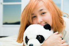 Pretty young woman lying comfortably on white bed. And hugging stuffed panda animal with large windows in background Royalty Free Stock Image