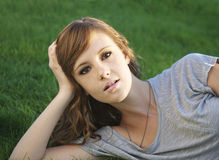 Pretty young woman lying on grass royalty free stock photography