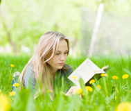Pretty young woman lying on grass with dandelions and reading a book Royalty Free Stock Images