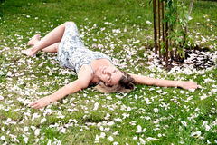 Young woman on a meadow surrounded by petals Royalty Free Stock Photo