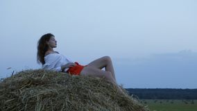 Pretty young woman lying on hay. Loop stock footage