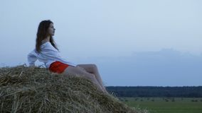 Pretty young woman lying on hay stock video footage