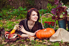 Pretty young woman lying near the vegetables in the autumn park Stock Photo
