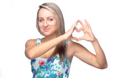 Pretty young woman making heart sign on white stock photos