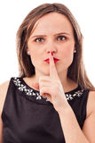 Pretty young woman making a keep it quiet gesture Royalty Free Stock Photo