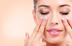 Pretty young woman massaging her face. Antiaging concept royalty free stock image