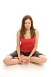 Pretty young woman meditating. A pretty young woman, isolated against a white background, meditates in the lotus position Stock Photo