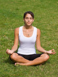 Pretty young woman meditating on grass Stock Photos