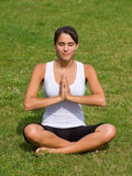 Pretty young woman meditating on grass Stock Photography