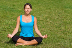 Pretty young woman meditating on grass Royalty Free Stock Photography