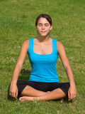 Pretty young woman meditating on grass Royalty Free Stock Photos