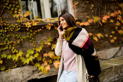 Pretty young woman with mobile phone. On street at autumn day Royalty Free Stock Images