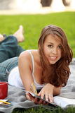 Pretty young woman model lying down reading. Pretty young woman model lying on a blanket outdoors reading on a summer day stock photos