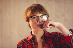 Pretty young woman with mustache on finger Royalty Free Stock Photography