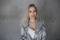 Pretty young woman with natural make-up with blond hair with blue eyes with sexy lips in a fashionable shirt in a stylish t-shirt. Near the vintage gray wall royalty free stock photography