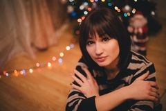 Pretty young woman near christmas tree in her cozy room Stock Photos