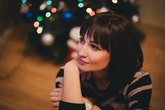 Pretty young woman near christmas tree in her cozy room Royalty Free Stock Photo